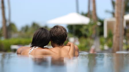 медовый месяц : Honeymoon couple relaxing together in an infinity swimming pool in luxury resort spa retreat beach destination. Luxurious hotel travel vacation. Unrecognizable people relaxed enjoying summer holidays.