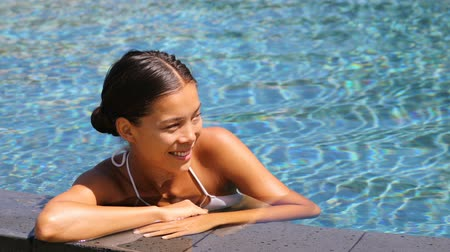 pływak : Bikini woman lying relaxing in infinity pool at luxury resort spa retreat. Beautiful mixed race woman sunbathing in swimsuit on the edge of pool enjoying the blue water. Getaway vacation Wideo