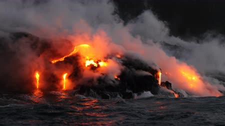 parecer : Hawaii Lava ocean close up - Lava running in the ocean from Kilauea volcano, Hawaii. Lava stream seem from lava boat tour flowing from volcanic eruption on Big Island, USA. Dawn Slow motion. Year 2016