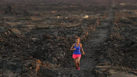 trilha : Running runner woman trail running cross country running outdoors on volcano. Female athlete jogging training for marathon run outside in beautiful landscape on Big Island, Hawaii, USA.