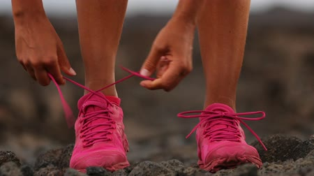 buty sportowe : Running woman tying shoe laces going running - girl trail runner. Closeup of female legs and running shoes in action. Girl athlete fitness runner running fast outside in trail running shoes. 59.94 FPS Wideo