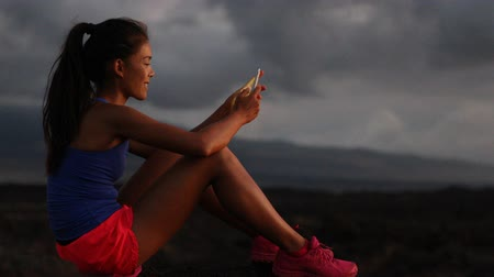 применения : Woman using smart phone looking at fitness tracking app after running at night. Running sport and fitness runner woman relaxing outside looking at smartphone screen. Healthy lifestyle. Стоковые видеозаписи