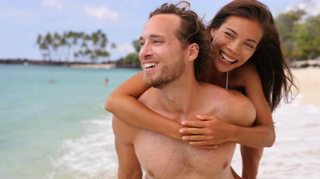 dospělý : Attractive happy couple laughing having fun piggybacking on tropical beach. Caucasian man carrying Asian girlfriend having fun laughing on travel vacation. Healthy happy interracial people. Beach life