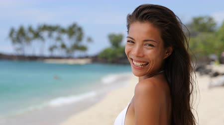 kahverengi : Cute happy Asian chinese woman laughing with perfect smile on paradise vacation tropical beach travel destination. Beautiful multiracial brunette girl in bikini sunbathing on ocean background. Stok Video