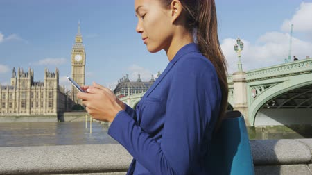 komoly : Business woman using phone sms texting on app in London, England. Young businesswoman using mobile phone walking in serious in suit jacket outdoors. Urban female professional by Westminster Bridge.