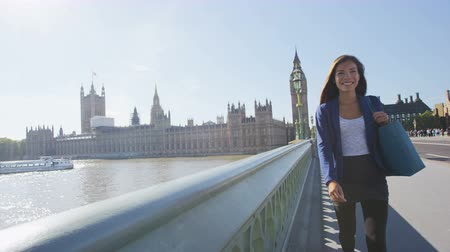 london england : Young urban professional woman walking in London with purse after shopping. Multicultural business woman walking on Westminster Bridge by Big Ben tourist attraction. RED EPIC SLOW MOTION.