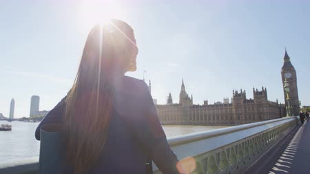 Лондон : Young urban professional business woman laughing and smiling walking on Westminster Bridge in London, England. Multicultural Asian Caucasian businesswoman enjoying her success. RED EPIC SLOW MOTION.