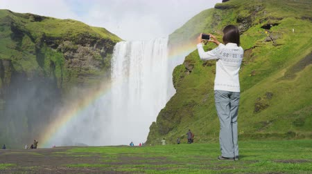 фотографий : Woman tourist by waterfall Skogafoss on Iceland taking photo with smart phone outdoor. Girl visiting famous tourist attractions and landmarks in Icelandic nature landscape, ring road route 1.