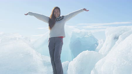 braços levantados : Happy joyful woman in Iceland standing on ice at Jokulsarlon Iceberg beach cheerful excited at Breidamerkursandur Ice beach by Jokulsarlon glacial lagoon. RED EPIC, 96 FPS, SLOW MOTION.