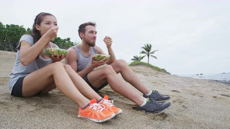 elvihető : Salad - healthy lifestyle couple eating salad after fitness workout on beach. Multiracial woman and man having a break on beach snacking on a vegan takeaway meal of green veggies laughing together. Stock mozgókép