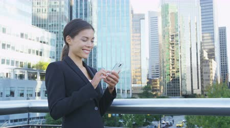 multikulturális : Business woman on phone sms texting using app on smartphone in city business district. Young businesswoman using smartphone smiling happy wearing suit jacket outdoors. Urban female professional.