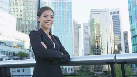 vezérigazgató : Business woman portrait of young female urban professional businesswoman in suit standing outside office building with arms crossed. Confident successful multicultural Chinese Asian  Caucasian woman. Stock mozgókép