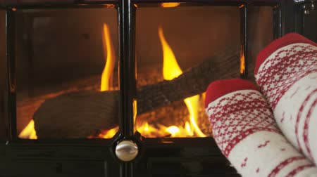 szekrény : Feet in warm socks in front of fireplace in winter. Woman wearing socks against fireplace in living room. Female is warming her legs during winter. SLOW MOTION shot Stock mozgókép