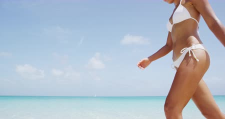 opalenizna : Skincare and bodycare concept with skin close up of woman in bikini walking on beach. Wideo