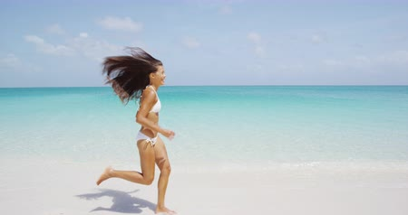 életerő : Cheerful woman in white bikini running at beach. Young female is enjoying nature during her summer vacation travel.