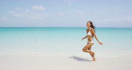 strand : Asian American girl happy having fun on beach on luxury island. Woman in bikini