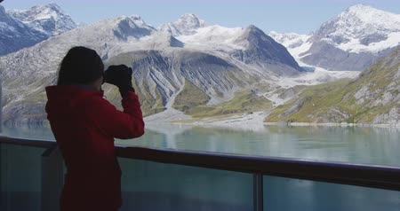 vacation destination : Tourist looking at Alaska Glacier Bay nature landscape using binoculars on cruise ship. Whale watching from boat.