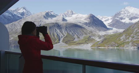 alasca : Tourist looking at Alaska Glacier Bay landscape using binoculars on cruise ship. Woman on vacation travel looking for wildlife enjoying cruising famous tourist destination.