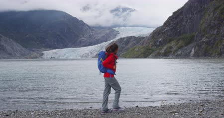 alasca : Tourist hiking woman in Alaska walking by Mendenhall Glacier landscape. Woman hiker on travel adventure trekking wearing backpack.