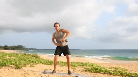 snatching : Fitness Dumbbell Snatch - man doing strength training fitness exercises with Dumbbells on beach. Fit male fitness model working out lifting free weights outdoors on beach.