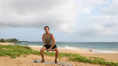 snatching : Fitness Dumbbell Snatch - man doing strength training exercises with Dumbbells on beach. Fit handsome male fitness model sweating during dumbbell workout exercise outdoors on beach. SLOW MOTION.