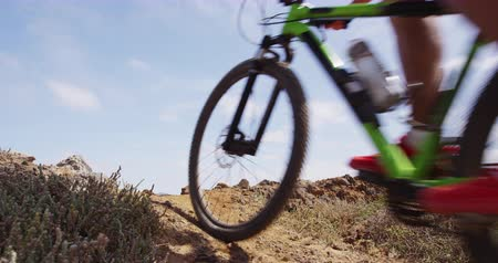 atleta : Mountain biker biking in slow motion on MTB mountain biking trail. Man in mountain bike race action close up of bike. SLOW MOTION.