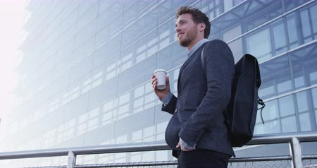 vezérigazgató : Businessman portrait of young male urban professional business man in suit standing outside office building. Confident successful young caucasian man drinking coffee wearing cool backpack. SLOW MOTION Stock mozgókép