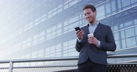 bebida : Business man drinking coffee using mobile cell phone app in city to play video games or text sms online. Young urban professional businessman enjoying coffee break relaxing using smartphone.