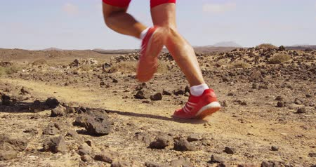 buty sportowe : Running man trail running in desert - male athlete running fast. Closeup of running legs and running shoes in SLOW MOTION. RED EPIC.