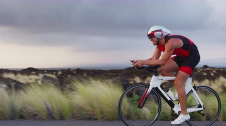 tijdrit : Triathlon fietsen - mannelijke triathlete fietsen op triathlon road bike. Fit man fietser op professionele triathlon fiets draagt ​​tri suit en time trail helm training voor Ironman. SLOW MOTION. Stockvideo