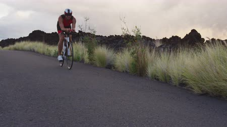 tijdrit : Triathlon fiets man - mannelijke triathlete fietsen op triathlon fiets. Fit man fietser op professionele triathlon fiets draagt ​​tri suit en time trail helm training voor Ironman. Van Big Island, Hawaii
