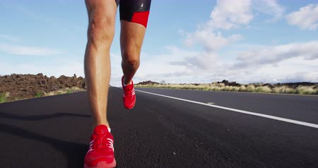 kimerül : Running shoes on male triathlete runner - close up of feet running on road. Man jogging outside exercising training for triathlon ironman. SLOW MOTION.