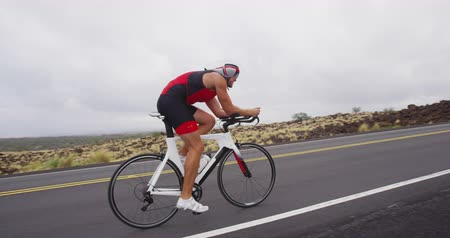 bicycle : Triathlon cycling - male triathlete biking on triathlon bike. Fit man cyclist on professional triathlon bicycle wearing time trail helmet for ironman race. From Big Island Hawaii. SLOW MOTION RED EPIC Stock Footage