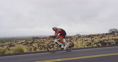 tijdrit : Triathlon fietsen - mannelijke triathlete fietsen op triathlon fiets. Fit man fietser op professionele triathlon fiets dragen tijdslot helm voor ironman race. Van Big Island Hawaii. SLOW MOTION RED EPIC Stockvideo