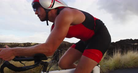 tijdrit : Fiets Triathlon man - mannelijke triathlete fietsen op triathlon fiets. Fit man fietser op professionele triathlon fiets draagt ​​tri suit en time trail helm training voor Ironman. Van Big Island, Hawaii