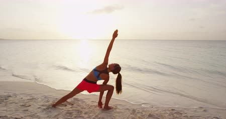 esneme : Yoga woman pose at beach at sunrise. Female yoga girl working out training in serene ocean landscape doing Extended Side Angle Pose. SLOW MOTION STEADICAM
