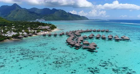 távozás : Tropical vacation paradise island with overwater bungalows resort in coral reef lagoon ocean by beach. Aerial video of Moorea, French Polynesia, Tahiti, South Pacific Ocean.