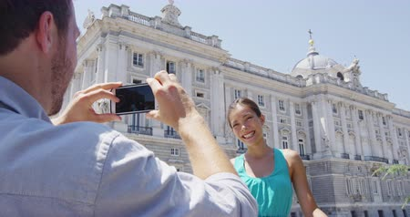 palacio real : Tourists taking photo on smart phone in Madrid. Romantic couple man and woman in love using smartphone taking photograph on travel in Spain by Palacio Real de Madrid.