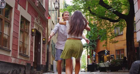 вокруг : Happy couple embracing in love romantic and fun. Woman running in the arms of her boyfriend man. Turning around swirling laughing joyful and cheerful. Urban city people in Gamla Stan, Stockholm Sweden