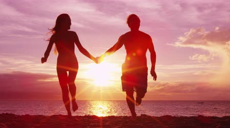 Beach couple holding hands on beach happy enjoying sunset running having fun on romantic summer travel vacation holiday honeymoon. Happiness and sunlight flare.  SLOW MOTION.