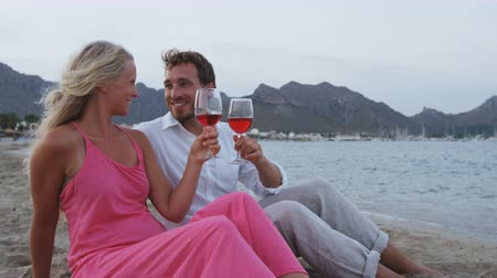 sparkling drink : Happy couple toasting wine glasses drinking wine on romantic date or honeymoon on beach. SLOW MOTION.