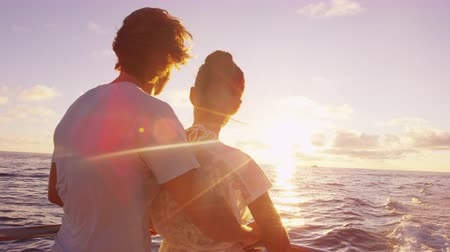 Cruise ship vacation couple enjoying sunset view sailing on small cruise boat at sea. Romantic couple on honeymoon travel at sea looking at sunset. SLOW MOTION. Dostupné videozáznamy