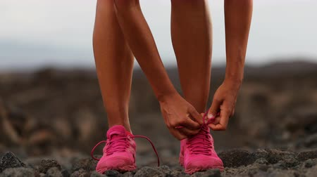 pink : Young female athlete tying shoelaces in arid landscape. Woman is wearing pink sports shoes. She is preparing to exercise in nature. Stock Footage