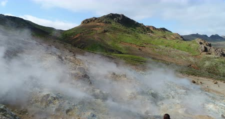 seltun : Iceland nature drone video of tourist taking pictures by volcano geothermal fields with volcanic activity of fumaroles. Seltun geothermal field in Krysuvik, Reykjanes peninsula, Iceland. Photographer.
