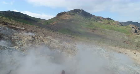 seltun : Iceland tourist near volcano geothermal field with volcanic activity fumaroles taking pictures in Seltun geothermal field in Krysuvik, Reykjanes peninsula. Iceland photographer