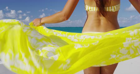 brazília : Beautiful sexy bikini body woman relaxing in yellow flowing cover-up beachwear fashion wrap on ocean sun background. Weight loss thighs cellulite and skincare spa beauty care concept.