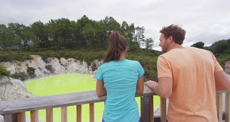 wai o tapu : New Zealand travel tourists looking at colorful green pond. Tourist couple enjoying famous attraction on North Island, geothermal pools at Waiotapu, Rotorua, New Zealand.