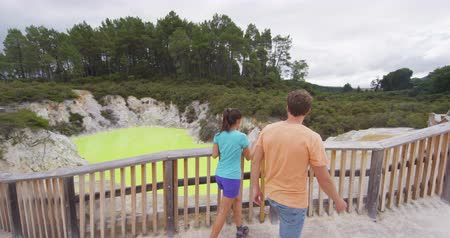 wai o tapu : New Zealand travel tourist couple looking at colorful green pond. Tourists enjoying famous attraction on North Island, geothermal pools at Waiotapu, Rotorua, New Zealand.