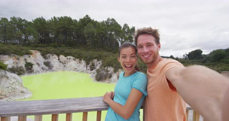 wai o tapu : New Zealand tourist attraction couple tourists taking selfie at famous travel destination, Waiotapu. Active geothermal yellow pond, Rotorua, north island. AKA Wai-O-Tapu, New Zealand. Stock Footage