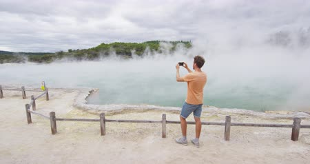 wai o tapu : New Zealand travel tourist taking phone picture of famous attraction Champagne pool, Waiotapu. Active geothermal area, Okataina Volcanic Centre, Reporoa, in Taupo Volcanic Zone, Rotorua, north island. Stock Footage